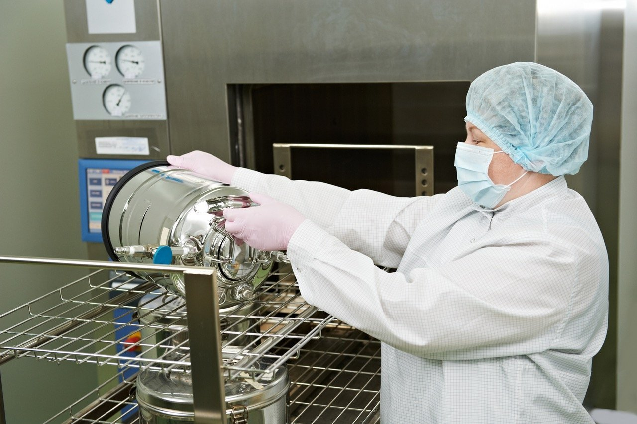 pharmaceutical factory. worker operating autoclave for medicine sterilization
