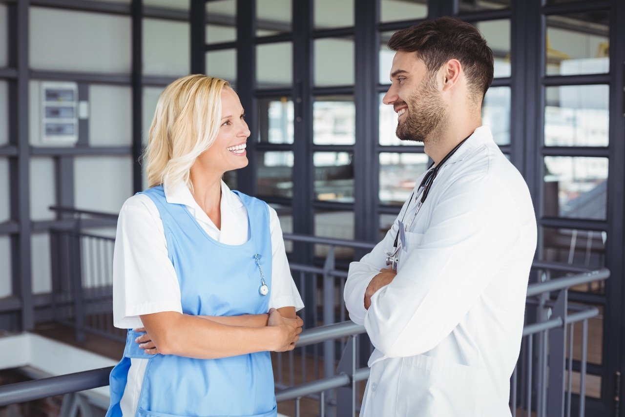 Happy doctors discussing while standing at hospital
