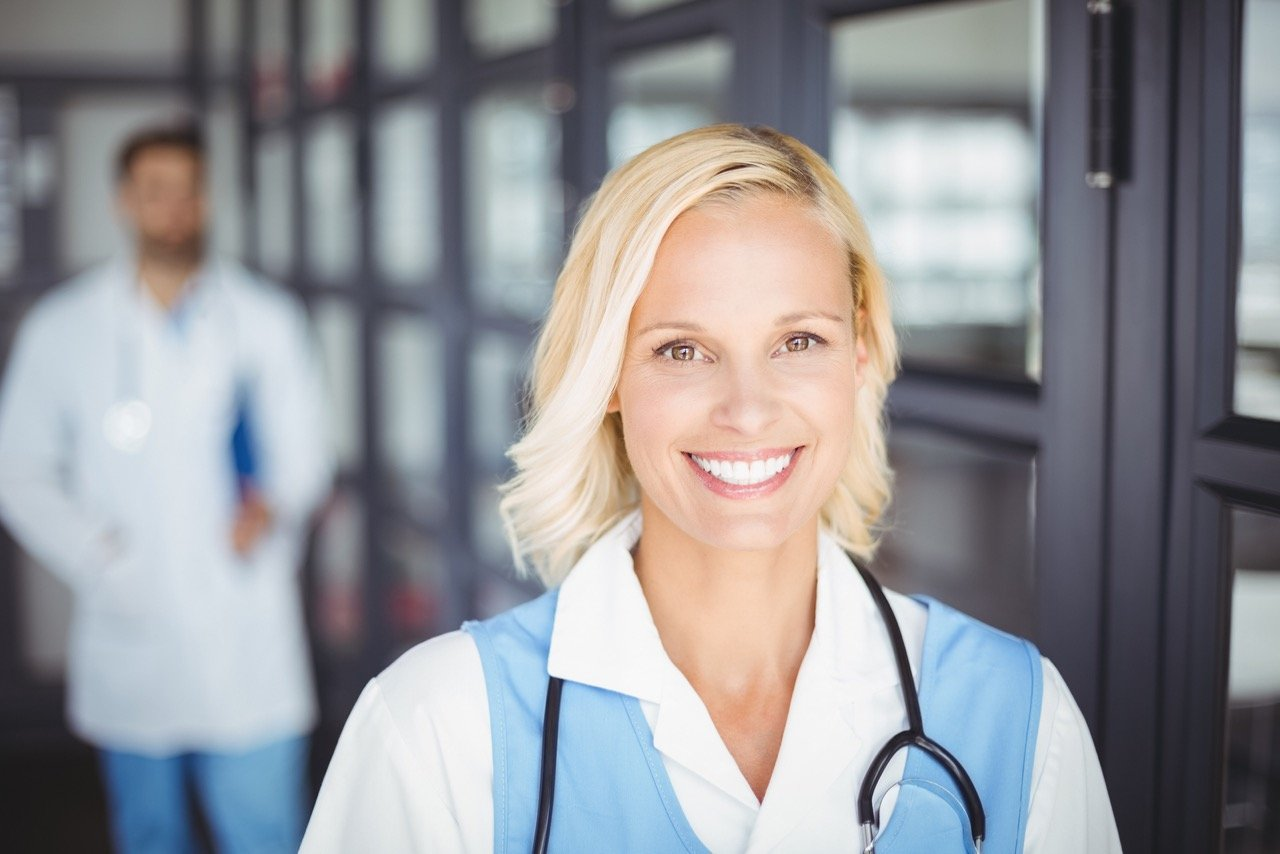 Portrait of cheerful female doctor standing in hospital