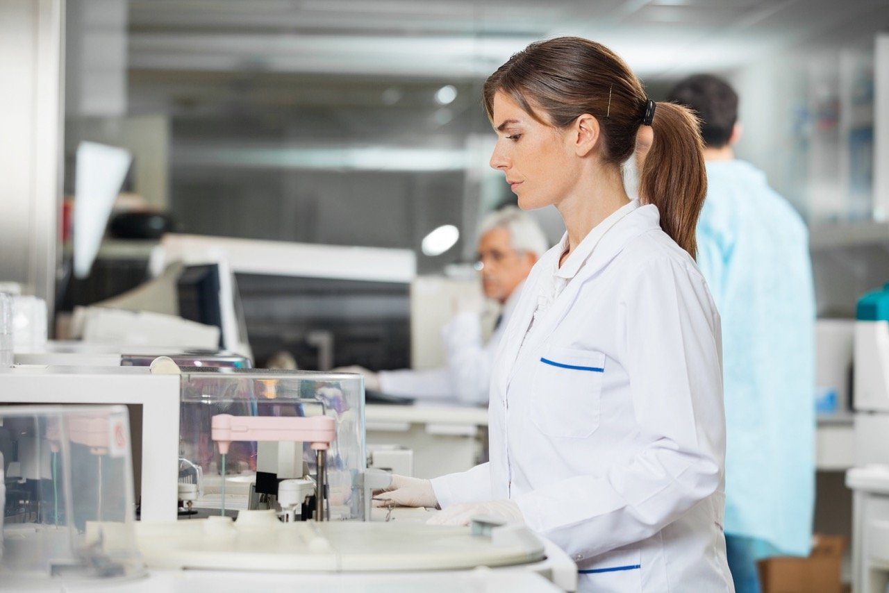 Side view of female researcher using centrifuge in medical lab