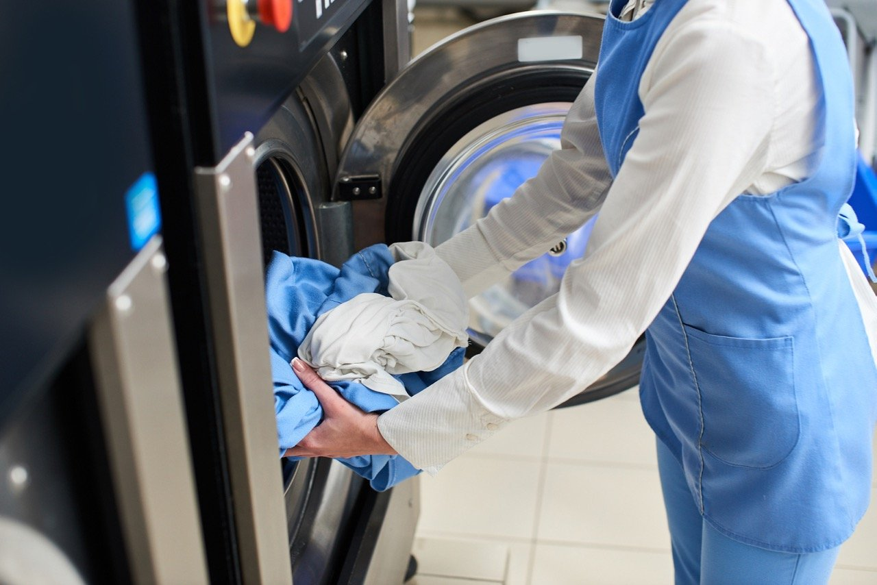 The worker loads the Laundry clothing into the washing machine at the dry cleaners