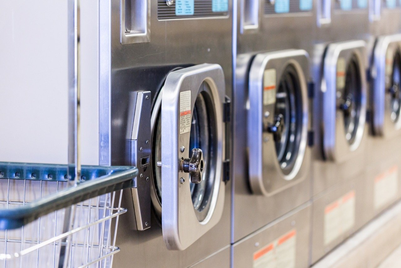 Industrial washing machines in a public laundromat.